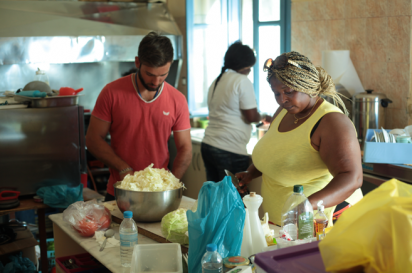Immigrant chefs cooking in the kitchen of Welcome Home in Lesbos, Greece.