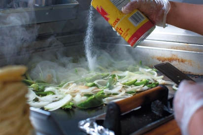 peppers and onions cooking on the griddle at El Coyote Dormilon in Elmhurst