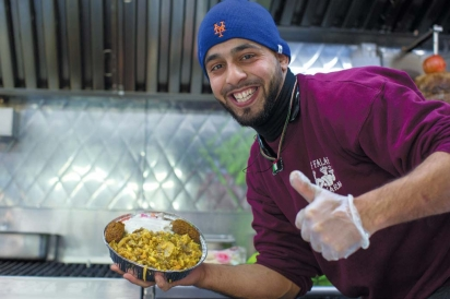 a server at King Falafel with an Omar Platter