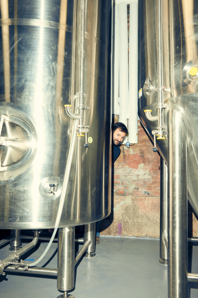 Owner, Chris Cuzme, hiding out behind one of Fifth Hammer Brewery's beer tanks.