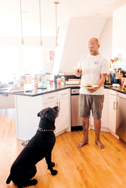Chef Whitney Aycock at home in Queens with his dog, Renzo, amidst his eclectic collections.